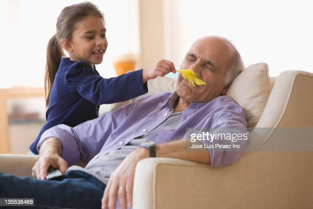 Granddaughter tickling sleeping grandfather with a feather