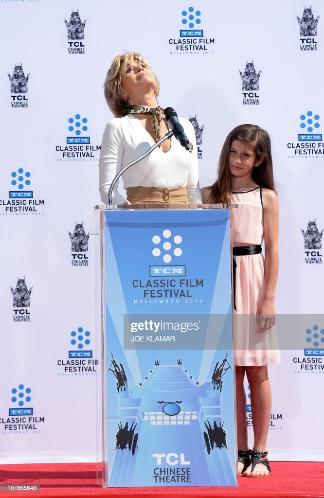 Granddaughter Viva Vadim listens as Jane Fonda looks up, speaking about her father, Henry Fonda, during Jane Fonda's Handprint/Footprint Ceremony during the 2013 TCM Classic Film Festival at TCL Chinese Theatre on April 27, 2013 in Los Angeles. Fonda is an American actress, writer, political activist, former fashion model, and fitness guru. She rose to fame in the 1960s with films such as Barbarella and Cat Ballou. She has won two Academy Awards, an Emmy Award, three Golden Globes and received several other movie awards and nominations during more than 50 years as an actress. After 15 years of retirement, she returned to film in 2005 with Monster-in-Law, followed by Georgia Rule two years later. She also produced and starred in over 20 exercise videos released between 1982 and 1995, and once again in 2010. AFP PHOTO/JOE KLAMAR