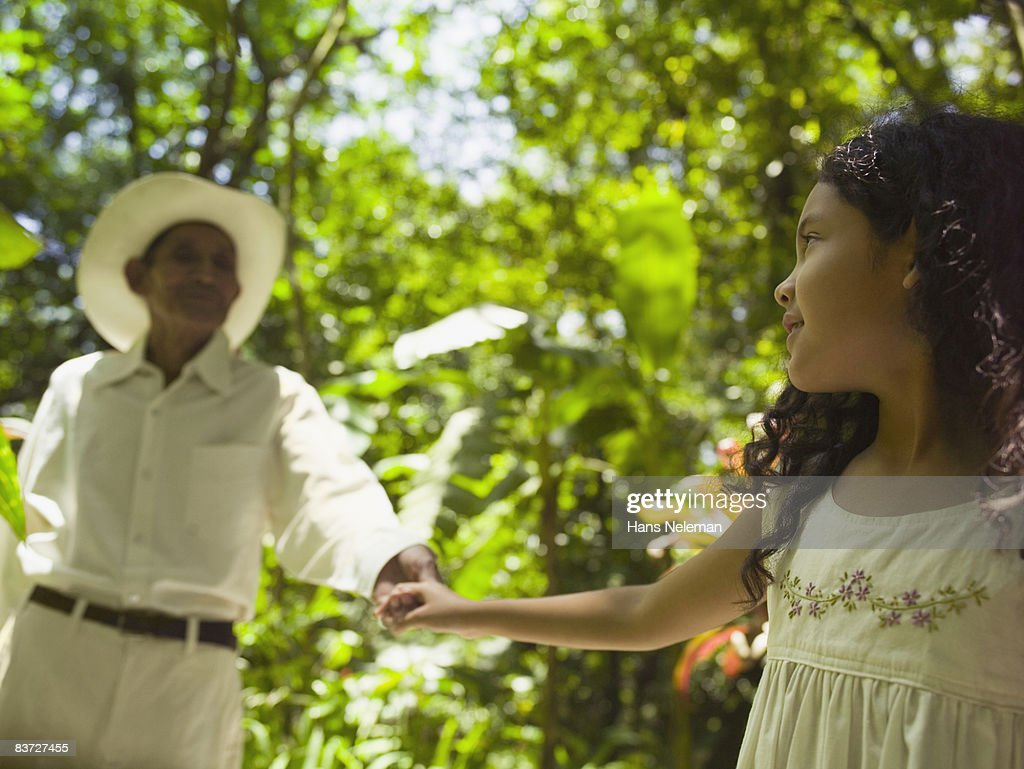 Granddaughter walking with grandfather in garden : Stock Photo