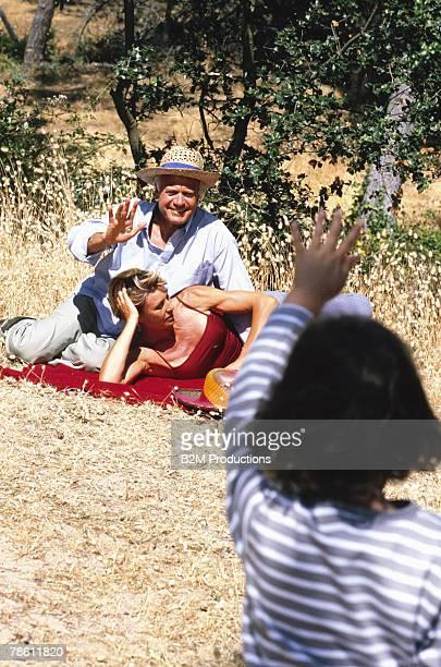 Granddaughter waving to grandparents having a picnic