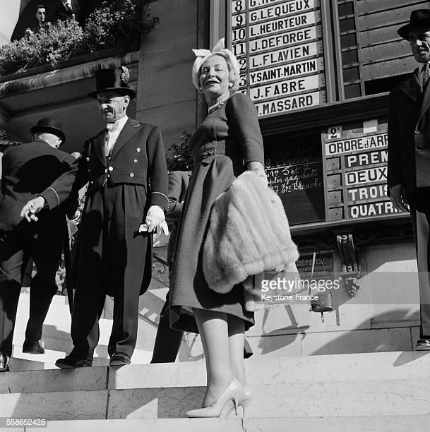 Grandes tenues pour les spectateurs venus assister à la course hippique sur la pelouse de Longchamp à Paris France le 4 octobre 1959