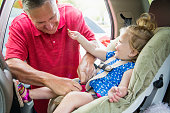 Grandfather adjusting granddaughter (12-23 months) into car seat