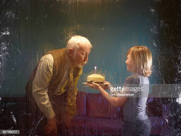 Grandfather and boy blowing out candle on cake
