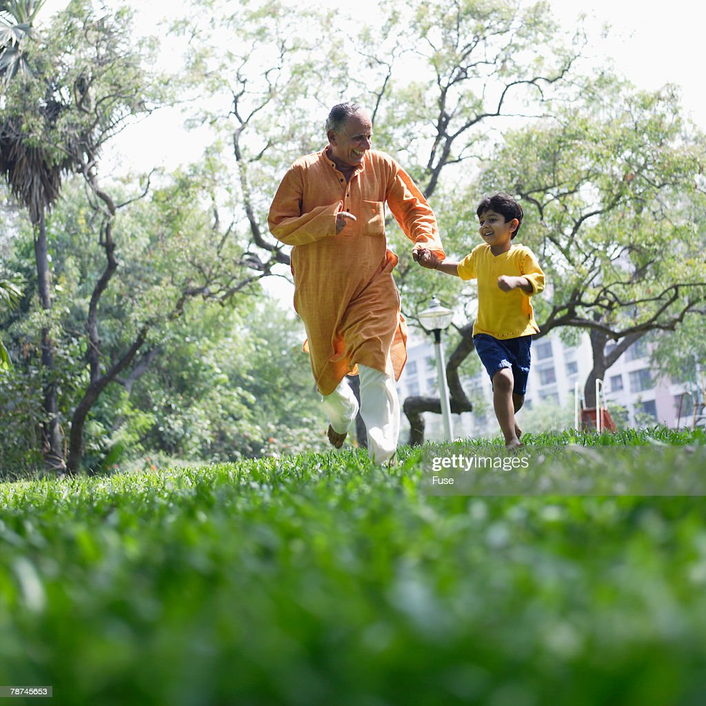 Grandfather and Boy Running in Meadow