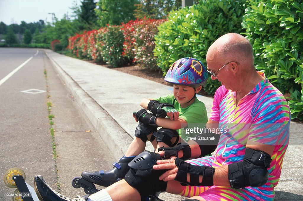 Grandfather and boy (7-9) sitting on sidewalk, wearing in-line skates : Stock Photo