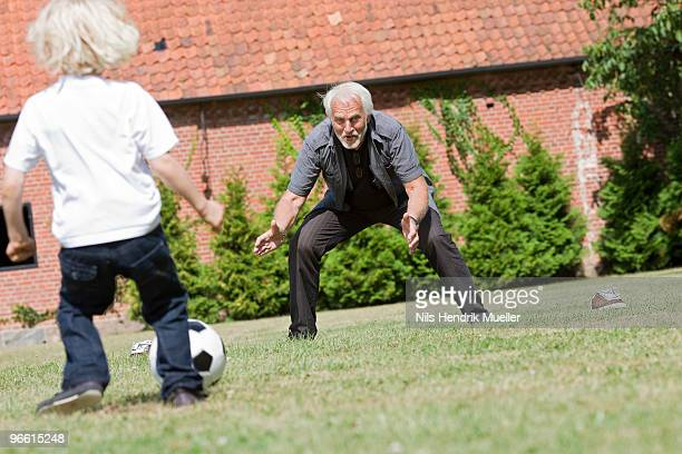 grandfather and child playing football