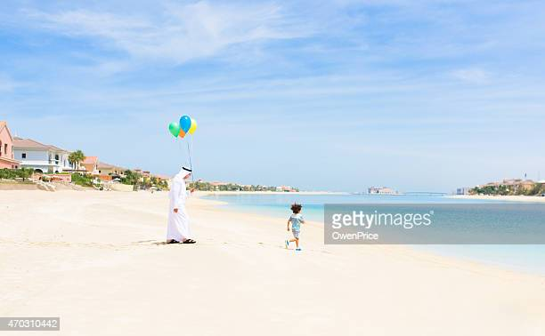 Grandfather and child walking on the Palm Jumeirah Beach