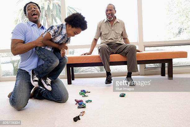 Grandfather and father playing with little boy