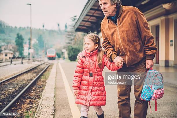 Nonno e ragazza in rosa a piedi alla stazione ferroviaria, l'Europa