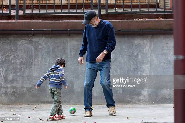 Grandfather and grandchild playing football