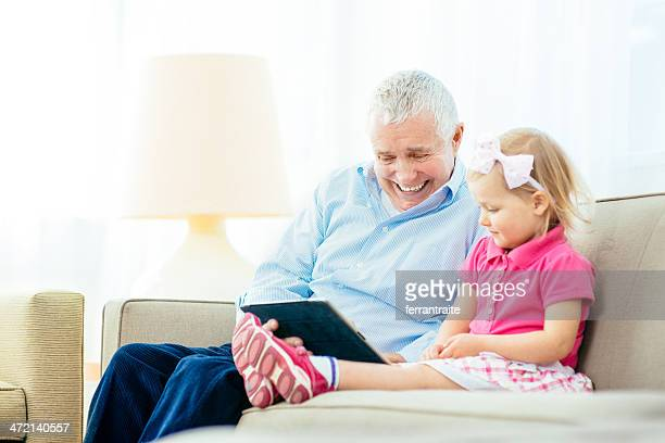 Grandfather and grandchild using digital tablet