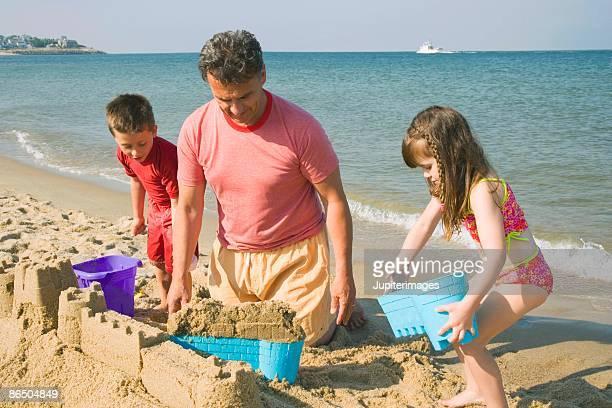 Grandfather and grandchildren building sand castle