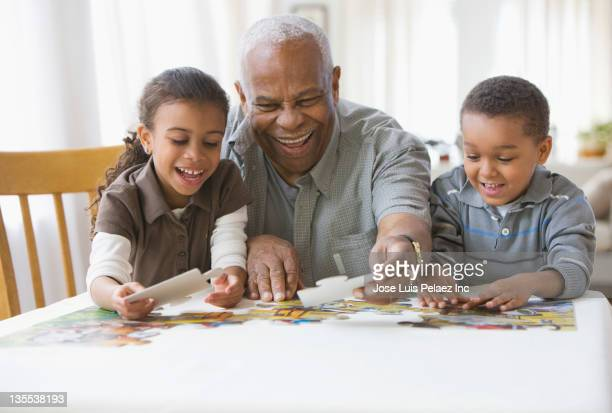Grandfather and grandchildren putting a puzzle together