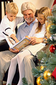 Grandfather and grandchildren reading at Christmas