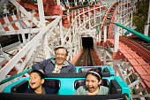 Grandfather and grandchildren (9-11) riding rollercoaster