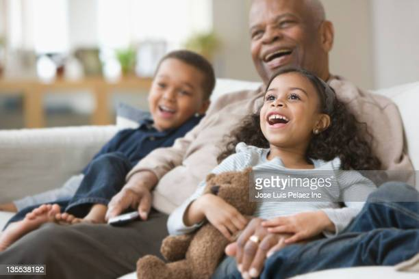 Grandfather and grandchildren watching television together