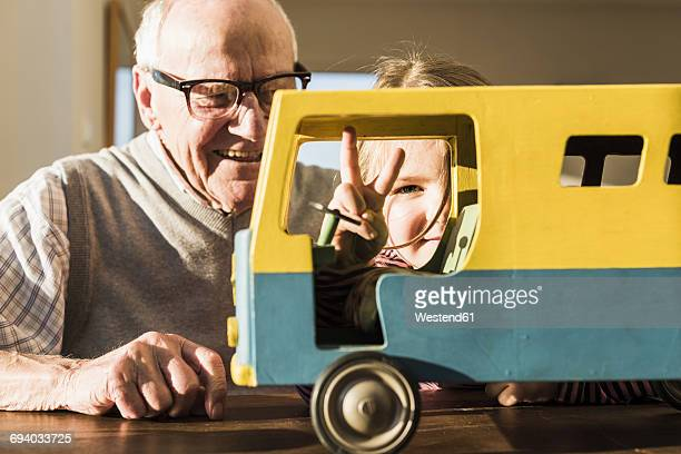 Grandfather and granddaughter assembling toy bus, girl making victory sign