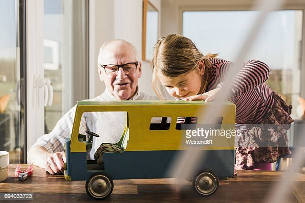 Grandfather and granddaughter assembling toy bus