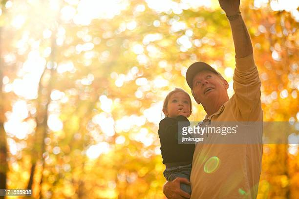 Grandfather and granddaughter autumn stroll.