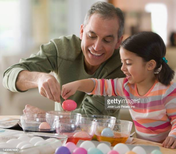 Grandfather and granddaughter decorating Easter eggs
