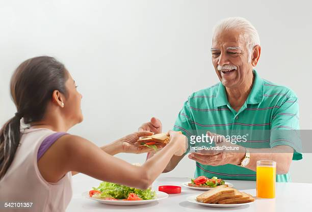 Grandfather and granddaughter eating breakfast
