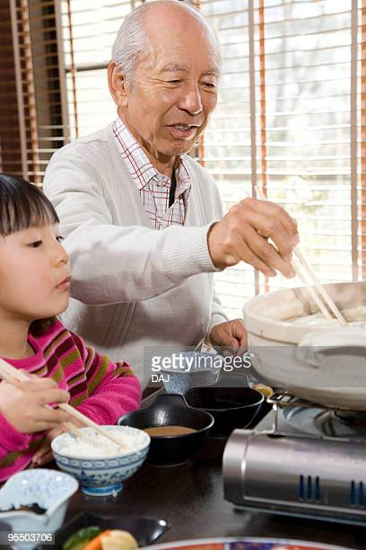 Grandfather and granddaughter eating