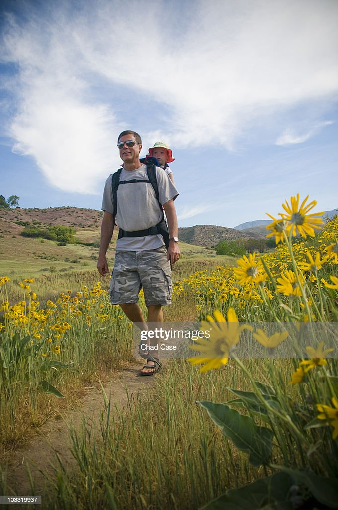 Grandfather and granddaughter hiking in a field of yellow flowers.