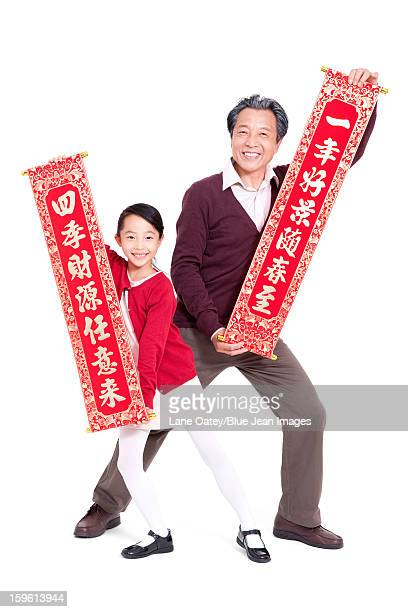 Grandfather and granddaughter holding Chinese New Year couplets