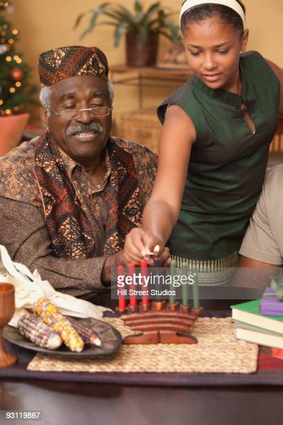 Grandfather and granddaughter lighting Kwanzaa candles