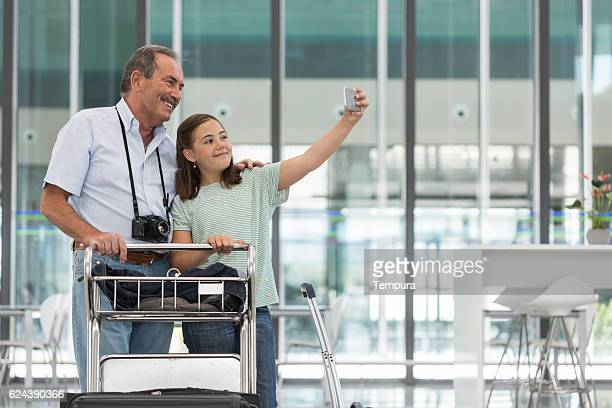Grandfather and granddaughter making a selfie before boarding