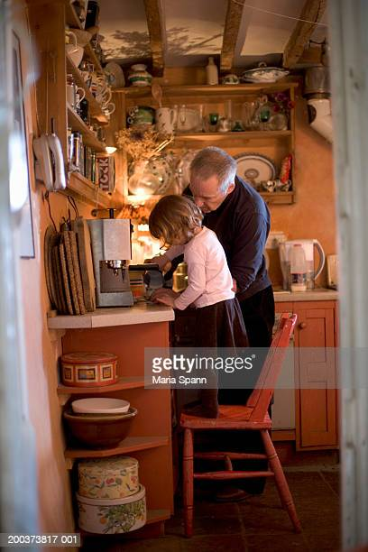 Grandfather and granddaughter (2-4) making cappuccino in kitchen, side view