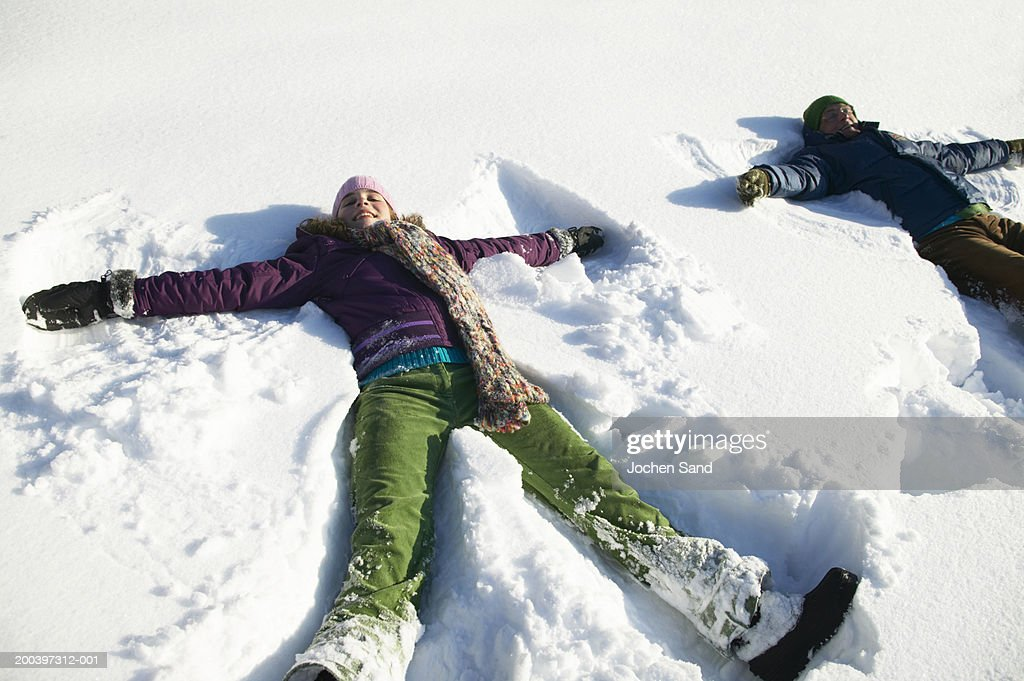 Grandfather and granddaughter (12-14) making snow angels, smiling : Stock Photo
