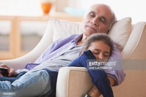 Grandfather and granddaughter napping in chair together