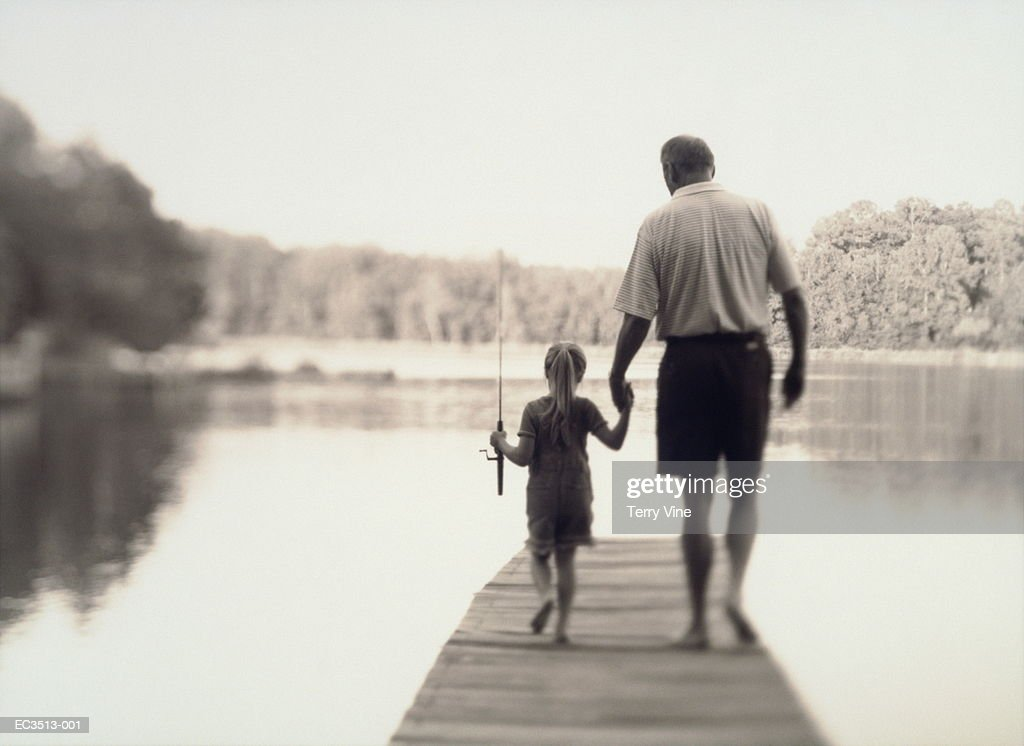 Grandfather and granddaughter (5-7) on jetty, rear view (toned B&W) : Stock Photo