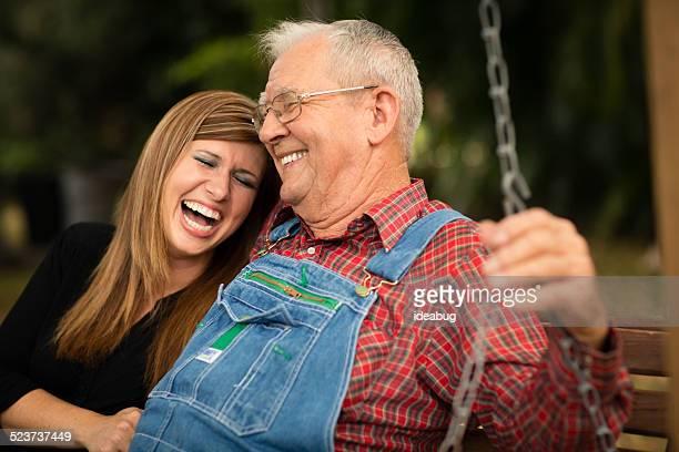 Großvater und Enkelin sitzend auf Schaukel zusammen
