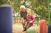 Grandfather and granddaughter playing on playground.
