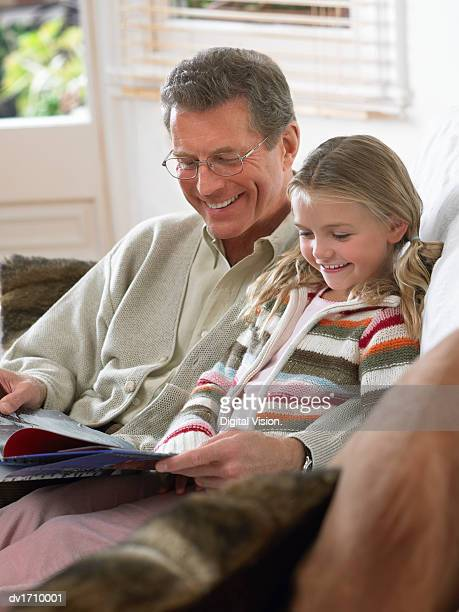 Grandfather and Granddaughter Sat Together on a Sofa, Reading a Book