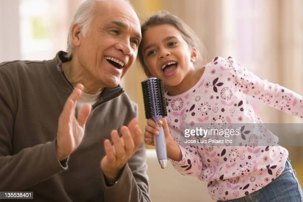 Grandfather and granddaughter singing together