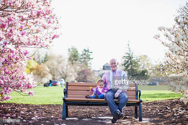 Grandfather and granddaughter sitting on park bench