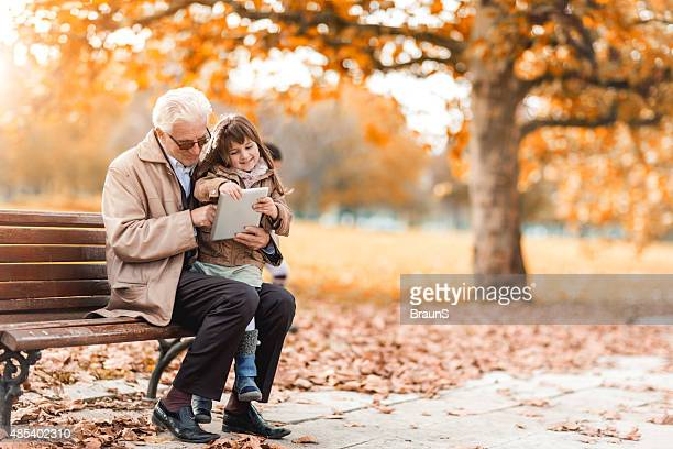 Grandfather and granddaughter using digital tablet in autumn.