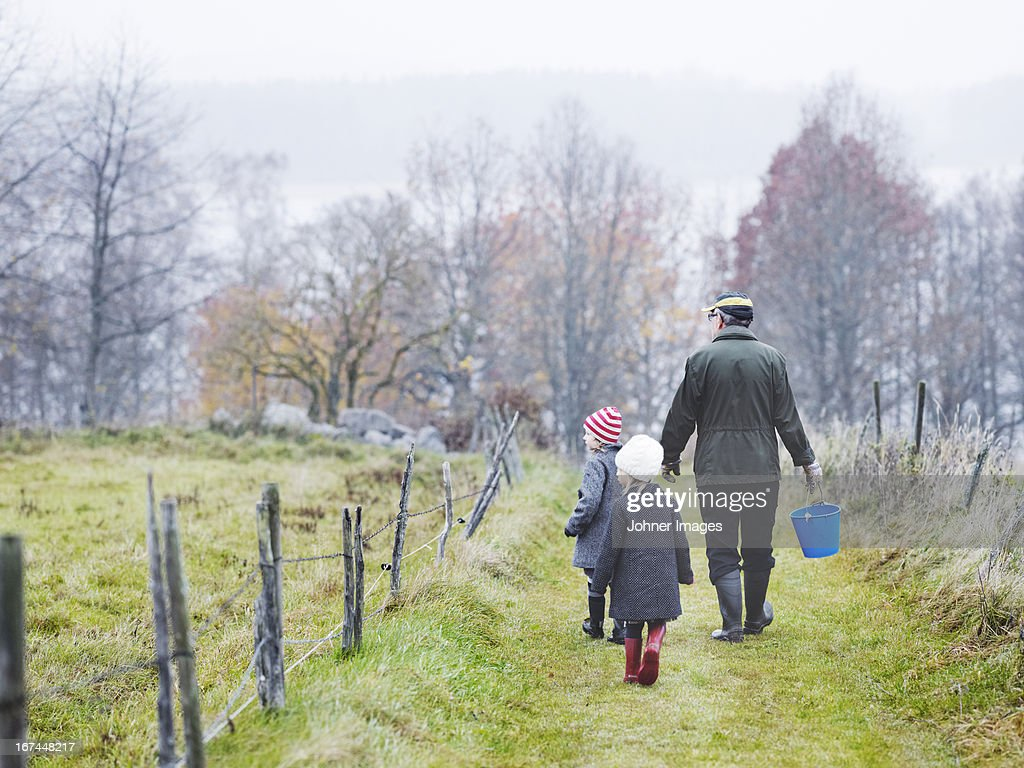 Grandfather and granddaughters walking on footpath : Stock Photo