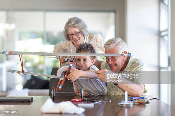 Grandfather and grandson building up a model airplane watched by grandmother