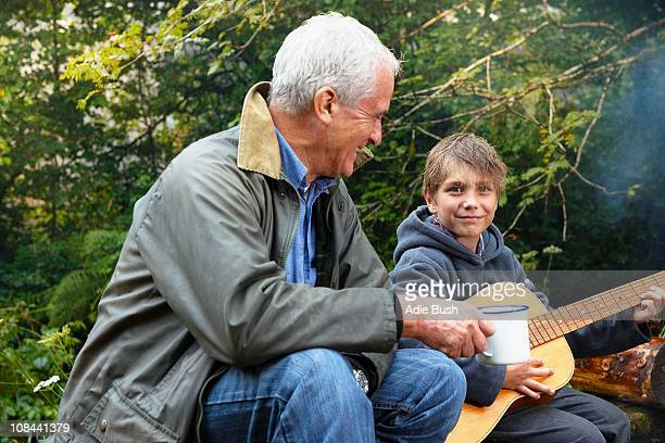 Grandfather and grandson by campfire