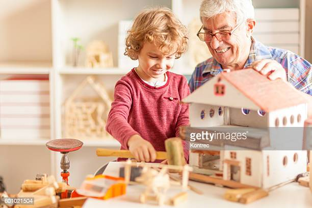 Grandfather and grandson crafting wooden toys