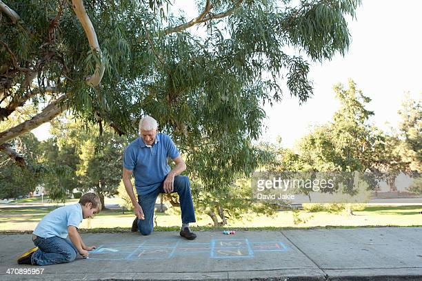 Grandfather and grandson drawing hopscotch