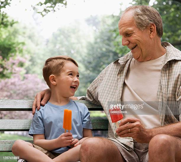 Grandfather and Grandson eating ice cream in a park