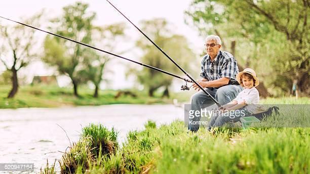 Grand-père et le petit-fils de pêche près de la rivière