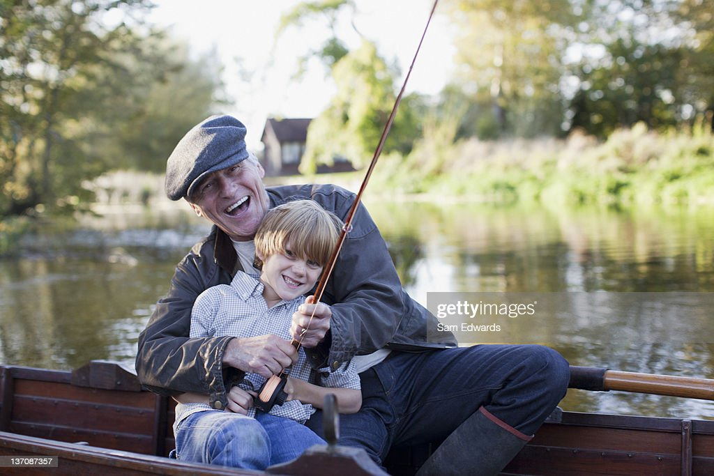 Grandfather and grandson fishing in boat : Stock Photo
