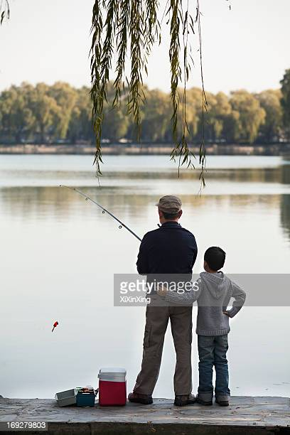 Grandfather and grandson fishing off of dock at lake