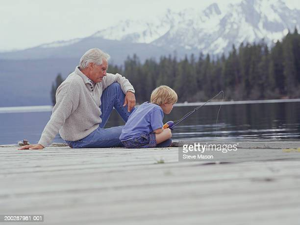 Grandfather and grandson (6-7) fishing on pier at lake